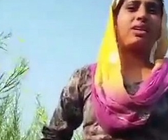 Desi girl removing glad rags in field.